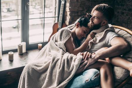 사랑하는 몇. 집에서 안락의 자에 앉아있는 동안 함께 휴식하는 담요로 덮여 아름 다운 젊은 부부