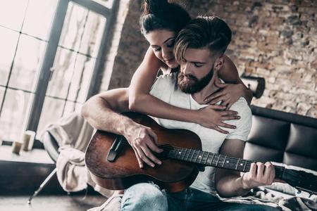 Guitar plezier. Knappe jonge bebaarde man zitten in bed thuis en gitaar spelen, terwijl aantrekkelijke vrouw hem omhelzen Stockfoto