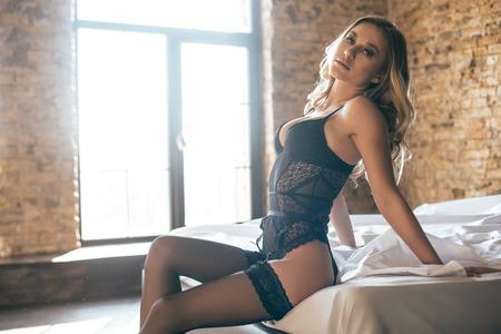 86a6ba9de52f #71441666 - Hermosa mujer joven y bella belleza en ropa interior negro  mirando a la cámara mientras está sentado en la cama en su casa