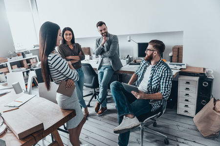 Important meeting. Handsome young man in casual wear and eyeglasses sitting on chair and holding digital tablet while discussing something with his colleagues in office Stock Photo