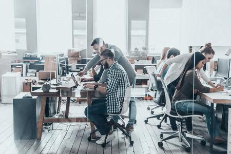 Het bespreken van zakelijke kwesties. Groep jonge mensen uit het bedrijfsleven zitten op het bureau en iets te bespreken, terwijl bij elkaar achter de glazen wand in de creatieve kantoor werken