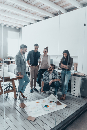 group strategy: Successful business team. Group of young modern people in casual wear planning business strategy while standing behind the glass wall in the creative office and looking at large blueprint laying on the floor Stock Photo