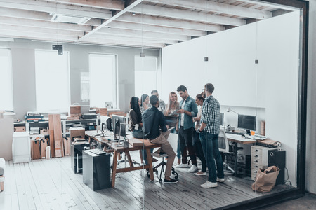 Succesvolle business team. Volledige lengte van jonge moderne mensen in smart casual wear met een vergadering tijdens het staan ??achter de glazen wand in de creatieve kantoor Stockfoto - 71539680