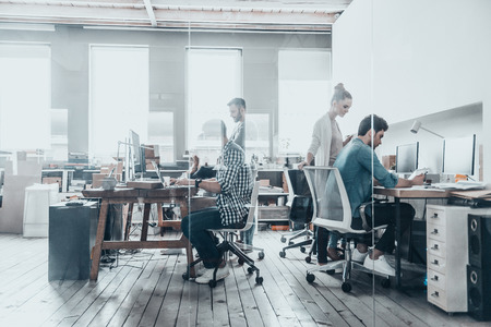 Successful professionals.  Group of business people using computers and communicating while working behind the glass wall in the creative office