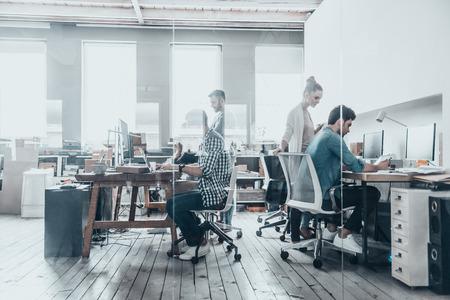 Succesvolle professionals. Groep van mensen uit het bedrijfsleven met behulp van computers en communiceren tijdens het werken achter de glazen wand in de creatieve kantoor Stockfoto