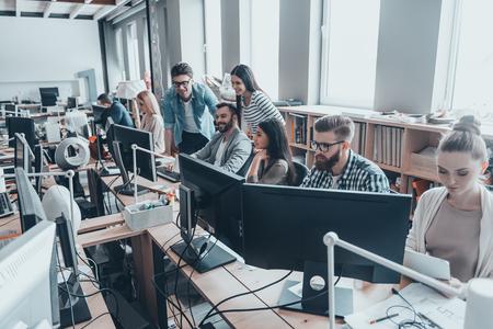 Beste team ooit. Groep van jonge ondernemers in slimme vrijetijdskleding samen te werken in de creatieve kantoor Stockfoto