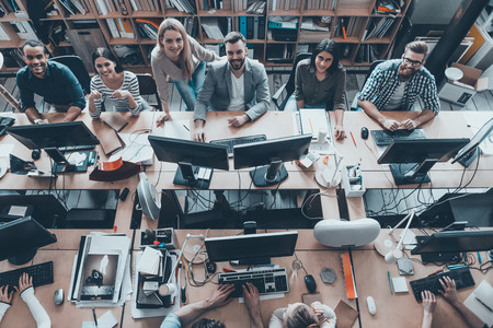 Young and successful. Top view of group of young business people in smart casual wear working together and smiling while sitting at the large office desk Archivio Fotografico