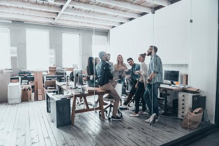 reunion de trabajo: Personas en el trabajo. Longitud total de jóvenes creativos en la ropa de sport inteligentes tienen una reunión de lluvia de ideas mientras está de pie detrás de la pared de cristal en la oficina creativa Foto de archivo