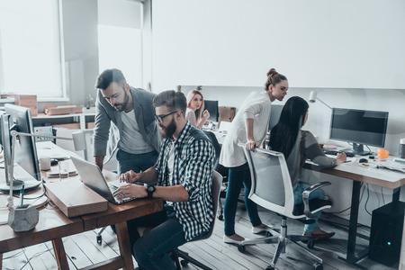 Het behalen van de beste resultaten. Twee zelfvertrouwen jonge mannen kijken naar laptop monitor terwijl hun collega's op de achtergrond werken Stockfoto - 71447190