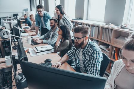 オフィスでの忙しい一日。スマートカジュアルの若いビジネス人々 のグループを着用する創造的なオフィスで一緒に働く