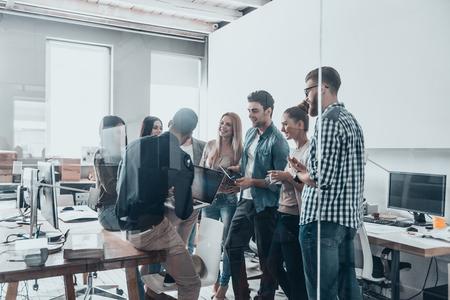 Lluvia de ideas juntos. Grupo de gente moderna jóvenes en el desgaste casual elegante que tiene una reunión mientras está de pie detrás de la pared de cristal en la oficina creativa