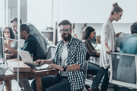 Happy to be a part of great team.  Young handsome man with beard smiling and looking at camera while sitting in office with colleagues working in the background