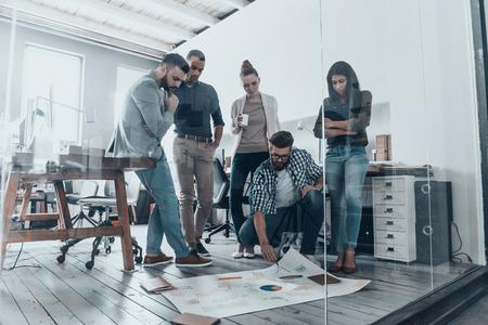 Strategie bespreken. Knappe jonge man met baard wijzen op groot papier tot op vloer, terwijl zijn collega's te kijken naar het
