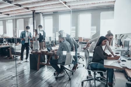 Úspěšný tým v práci. Skupina mladých podnikatelů, kteří pracují a komunikují společně v kreativní kanceláři Reklamní fotografie
