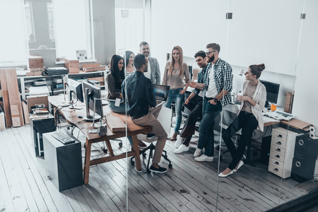 Team of innovators.  Full length top view of young modern people in smart casual wear talking and smiling while standing behind the glass wall in creative office