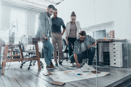 group strategy: Discussing strategy. Group of confident business people discussing something while standing in creative office and pointing at large paper lying on floor Stock Photo