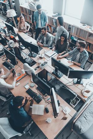 Éxito del equipo joven en el trabajo. Vista superior del grupo de jóvenes empresarios en ropa casual inteligente trabajando juntos mientras se sienta en el escritorio de la oficina grande Foto de archivo