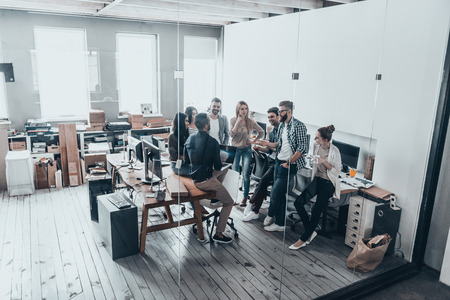 Cooperation in action.  Full length top view of young business people in smart casual wear talking and smiling while having a brainstorm meeting in office