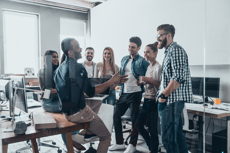 Young professional team.  Group of young modern people in smart casual wear having a brainstorm meeting while standing behind the glass wall in the creative office Banque d'images