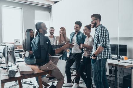 Jonge professionele team. Groep jonge moderne mensen in smart casual wear met een brainstorm bijeenkomst, terwijl die achter de glazen wand in de creatieve kantoor Stockfoto
