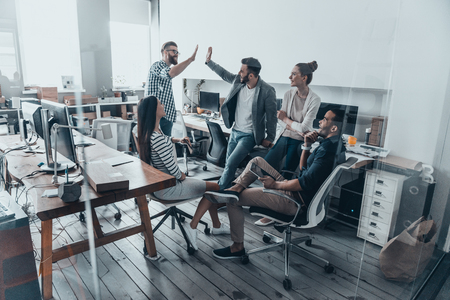 Vysoká pět pro úspěch! Dva veselí mladí podnikatelé dávají vysoko-pět, zatímco jejich kolegové se na ně dívají a usmívají se Reklamní fotografie