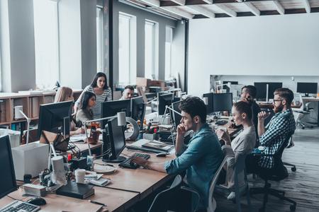 Besetzt Arbeitstag. Gruppe von jungen Geschäftsleute, die bei ihrer Arbeit zu konzentrieren, während im Büro am großen Schreibtisch sitzen zusammen