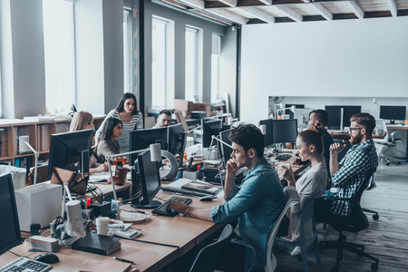 Journée de travail. Groupe des jeunes gens d'affaires se concentrant sur leur travail alors qu'il était assis au grand bureau de bureau dans le bureau ensemble Banque d'images - 71537725