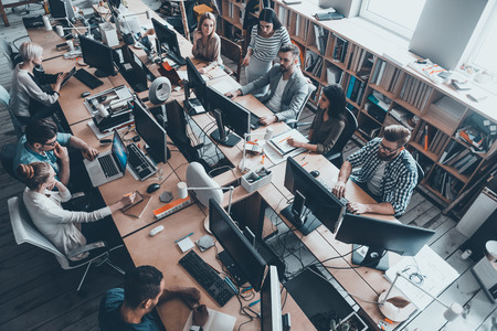仕事に自信を持ってビジネスの専門家。スマートカジュアルの若いビジネス人々 のグループの平面図を着用する大きい事務机に座りながら一緒に作