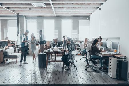 Tým při práci. Skupina mladých podnikatelů v inteligentní oblečení pro volný čas pracují společně v kanceláři tvůrčím