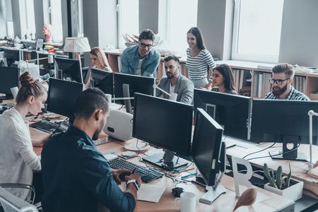 オフィスの稼働日。スマートカジュアルの若いビジネス人々 のグループを着用する創造的なオフィスで一緒に働く