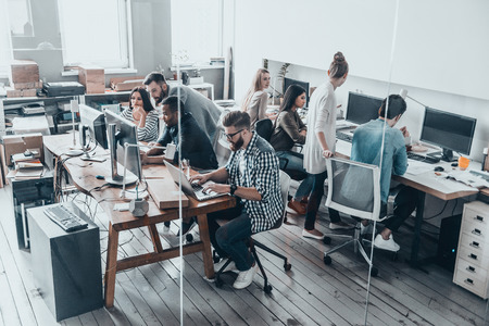 Zeker en succesvol team. Bovenaanzicht van jonge moderne mensen in smart casual wear te concentreren op hun projecten, terwijl bij elkaar achter de glazen wand in de creatieve kantoor werken Stockfoto - 71537724