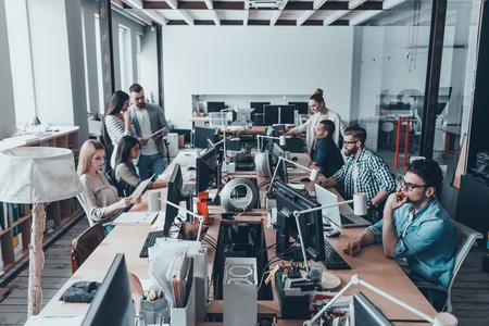 Drukke werkdag in het kantoor. Groep van jonge ondernemers in slimme vrijetijdskleding werken en communiceren tijdens de vergadering op het grote bureau in het kantoor samen