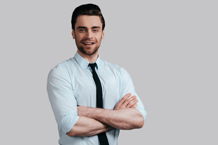 Confidence and charisma. Handsome young smiling man in white shirt and tie keeping arms crossed and looking at camera while standing against grey background Stock Photo