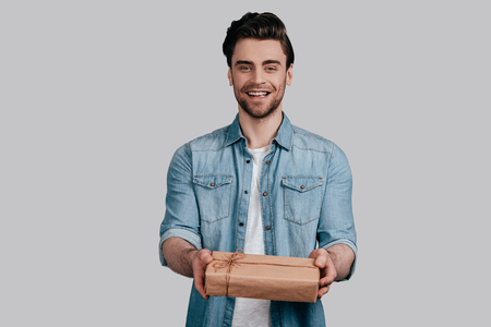 Gift for you! Handsome young man in blue jeans shirt giving a gift box and looking at camera while standing against grey background