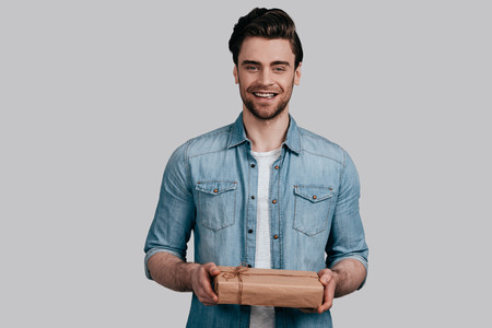 With love for you. Good looking young man in blue jeans shirt holding a gift box and looking at camera while standing against grey background