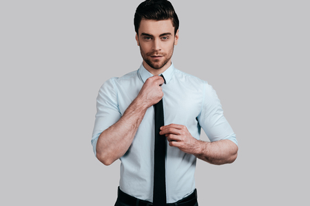 Used to look perfect.  Good looking young man in formalwear looking at camera and adjusting his tie while standing against grey background Stock Photo
