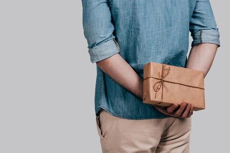 Surprising her... Close-up rear view of man in blue jeans shirt holding a gift box behind his back while standing against grey background Stock Photo