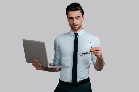 Confident business expert. Good looking young man in white shirt and tie holding laptop and eyeglasses while standing against grey background Stock Photo