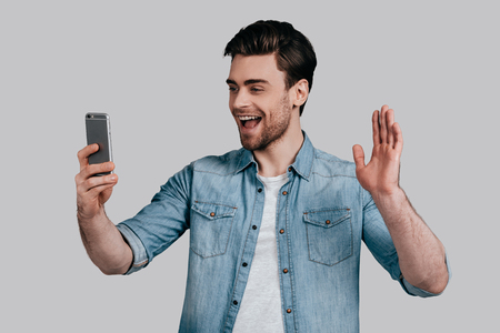 Hello! Good looking young man in blue jeans shirt waving and smiling while looking at his smart phone and standing against grey background photo