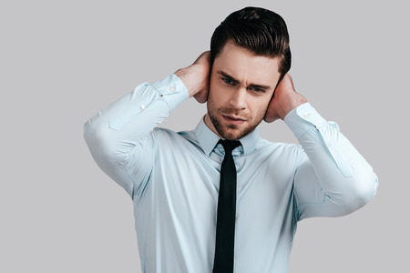 Feeling depressed. Frustrated young man in formalwear touching his head with hands and looking at camera while standing against grey background photo
