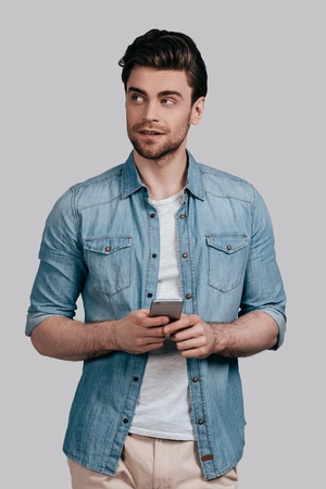 Thinking about? Good looking young man in blue jeans shirt holding smart phone and looking away while standing against grey background photo