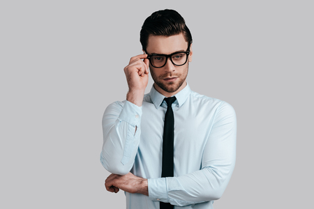 Taking everything seriously. Good looking young man in white shirt and necktie keeping arms crossed and adjusting his eyeglasses while standing against grey background photo