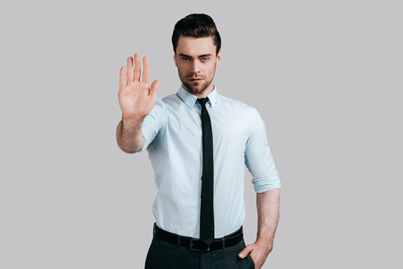 man shirt: No way to cheat him! Serious young man in white shirt and tie gesturing and looking at camera while standing against grey background