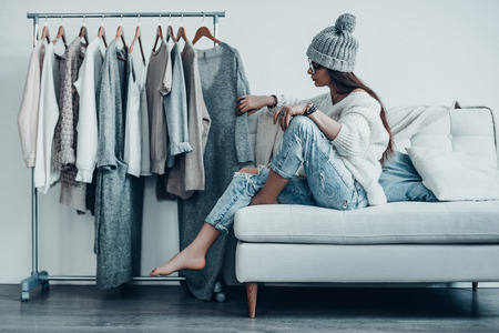 Maybe this one?  Thoughtful young woman in casual wear choosing the dress while sitting on the couch at home near her clothes hanging on the racks Stock Photo