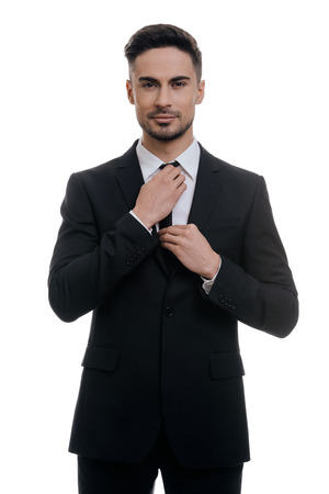 Used to look perfect. Handsome young man in full suit adjusting his necktie and looking at camera while standing against white background