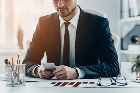 Using modern technologies at work. Close-up of young man in full suit holding smart phone while sitting at the office desk