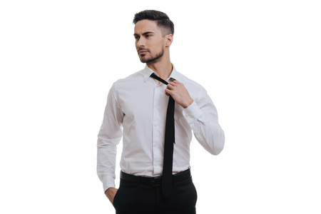 young businessman: Feeling tired.  Exhausted young man in formalwear looking away and taking off his tie while standing against grey background