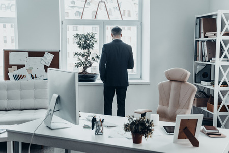 computer office: Hard working day. Rear view of young man in full suit standing near the window in the office