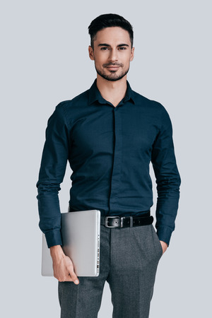 young businessman: Confident businessman. Good looking young man in shirt carrying laptop and looking at camera with smile while standing against grey background