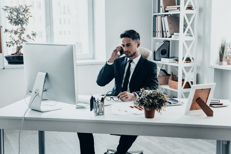 office man: Important business talk. Serious young man in formalwear talking on the phone while sitting at the office desk